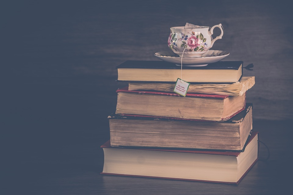 a stack of books with a floral teacup on top