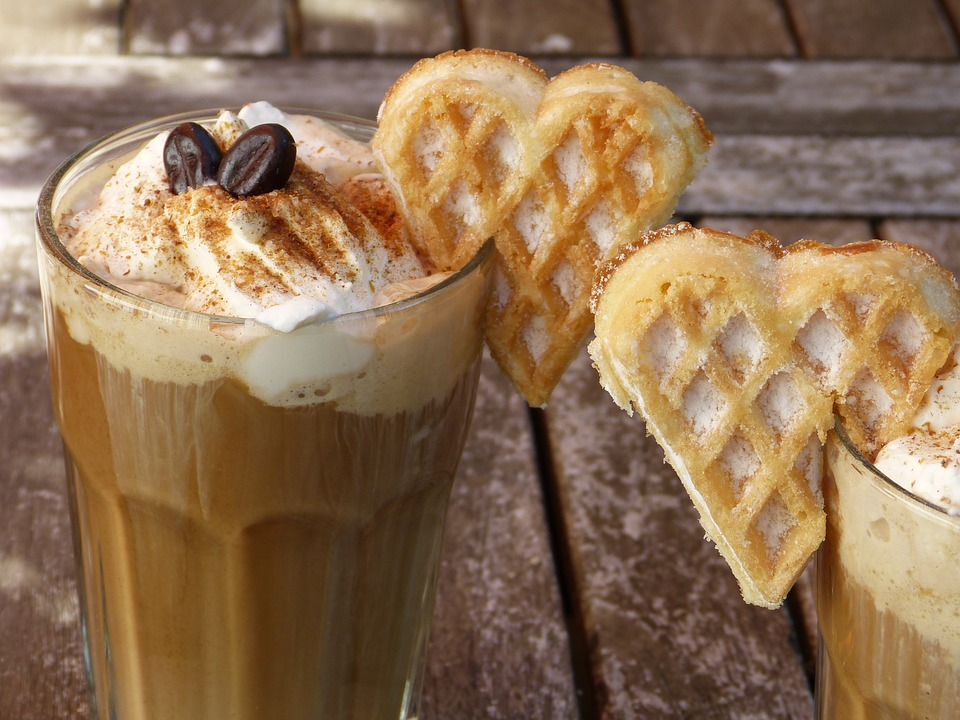 Two cups of ice coffee with cream and heart shaped waffles
