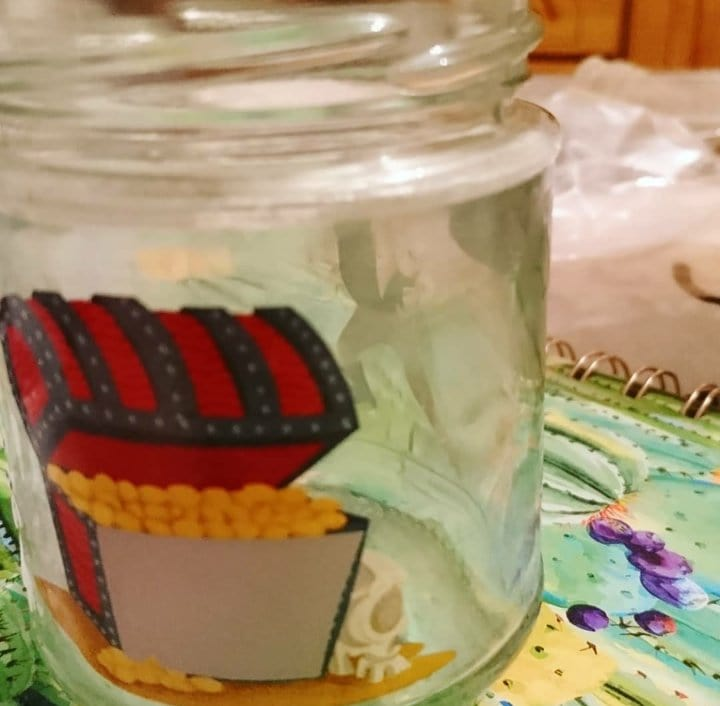 Empty jar with treasure chest sticker to be used as a flower pot