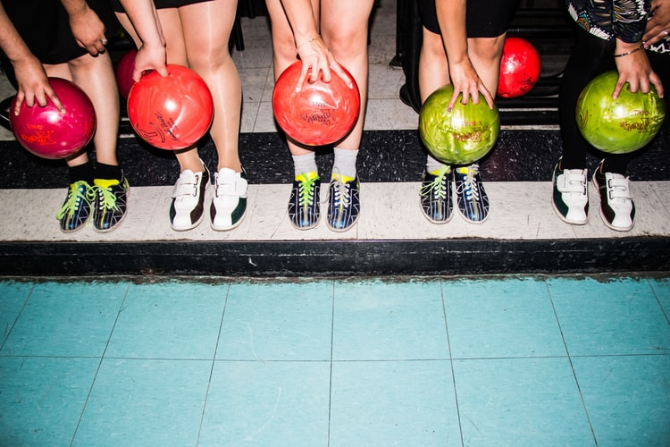 five friends holding bowling balls