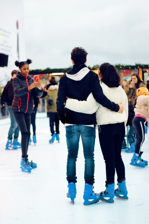 a couple getting their picture taking ice-skating